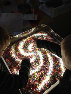 This looks like a sensory clear container with colored beads on top of a light table. Wonderful sensory and discovery activity at Ekuddens förskola, Bubblan ≈≈ http://www.pinterest.com/kinderooacademy/light-shadow-reflection-play/