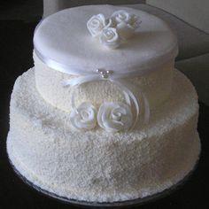 piętrowy tort bez lukru obsypany wiórkami plus lukrowe kwiaty