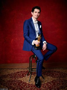 Looking good: La La Land director Damien Chazelle was also on hand to show off his prize, posing on a stool in his blue dinner suit