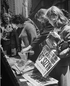 Women eagerly picking up the New York World - Telegram Newspapers with the headline 'NAZIS GiIVE UP' `