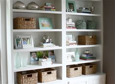 1. Books and baskets evenly spaced were the base that anchored the arrangement. 2. Family photos and sentimental items were placed at eye level giving them center stage. 3. Attractive filler accessories in a common color (sea glass green) unified the display. 4. I finished with a little bling. Mercury glass accessories added sparkle and depth.