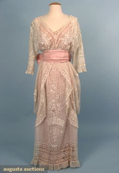 Hobble-style tea gown, circa 1913 (front.) One-piece dress fashioned from various laces including Val, torchon, and embroidered net. The skirt panels are embroidered with flower baskets. Wide pink brocade silk sash.