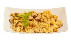 hot risotto with mushrooms on white plate on white background