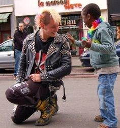 M. Lambrechts took this picture at a gay pride parade in Brussels 2009. This was a little kid of a gay couple coming to check those curious pins on his jacket. He pulled the punks jacket and the punk went sitting on his knees, when the 2 men called their kid back the punk got a little kiss from the kid.