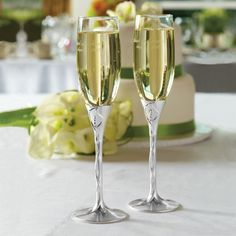 Personalized calla lily toasting flutes feature a floral design, brushed and polished silver-plated finishes accented with twinkling crystals.