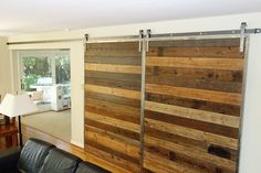 Doors were created from reclaimed planks set horizontally in a frame that matches the Stainless Steel Classic flat track hardware.