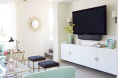 Flatscreen TV in girly living room with gold mirror, matching stools and glass coffee table