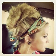 Retro bun = tease all roots of hair underneath. Turn head upside down and collect hair to a ponytail covering all roots.  Secure with elastic. Take loose hair im ponytail and bunch up to center for a sloppy bun. Then secure remaining strands of hair under elastic. Finish with headband or hair wrap. Use a pick to tease out sections of pulled back hair for volume. Use a fine most spray to finish off.