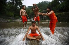 A Hindu devotee is poured with water by his friends as they take part in the