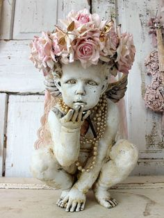 Cherub statue adorned pink rose crown shabby cottage chic distressed ornate angel w/ pearls and heart adornments home decor anita spero design  The cherub is 15 tall. I painted this cherub in a homemade faux plaster white paint and distressed it to add age, texture and character. I made the crown using handmade romantic pink roses which are hand dyed. In between the roses are tiny bits of golden leaves. There is a thin strip of salvaged rhinestones at the bottom. I adorned the neck with…
