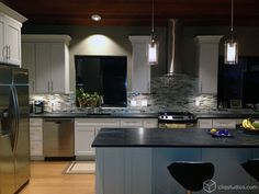 A gorgeous large white kitchen with black marble countertops and a beautiful textured tile backsplash. Cabinets from CliqStudios.com