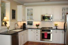 cuisine blanche avec plan de travail noir aux murs partiellement en brique blanche