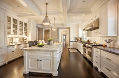 A white and dark wood kitchen featuring an elegant coffered ceiling and a white marble island. The expanse of countertops ensures that there is never a shortage of space to accommodate multiple cooks in the kitchen.
