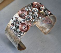 """""""Metal Garden Blooms""""  Copper, brass and sterling cuff bracelet, by Enter The Flame Studios,  artist, Brea Moser Anderson  $270  www.etsy.com/shop/entertheflame"""