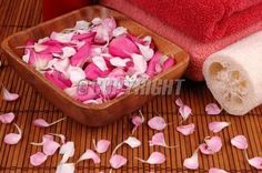 Towels, carnation and rose petals, and bath sponge in a spa