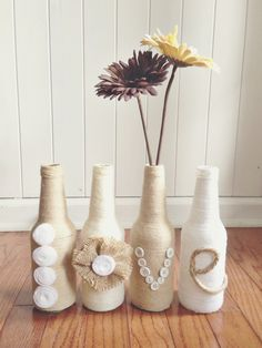 #Upcycle glass bottles using yarn, #burlap, and embellishments to create amazing home decor. Materials needed: glass bottles, yarn, felt, buttons, burlap, and Elmer's glue. #DIY