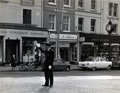 """White gloves at the ready, directing traffic near the Gas Consumers Co. store at the top of Patrick's Cork City, Street Photographers, White Gloves, Photo Essay, St Patrick, 1960s, Ireland, Street View, Times"