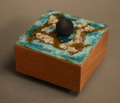 The base of this little handmade box is made from solid Mahogany, and finished with oil and a hard clear final coat. The bottom is Baltic Birch with a clear coat and black felt inside the box on the bottom. The removal top is handmade fused glass made to fit snugly on the top of the Box. An ebonized round knob in the center of the top is used to remove the top. Four round ebonized feet space the box off the table slightly. It's a signed piece, completely hand made in my studio here in…