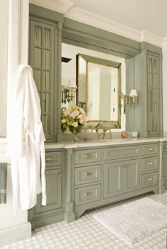 White and gray mosaic floor tiles lead to a stunning green gray washstand donning polished nickel cup pulls and a carrera marble countertop fitted with an antique hook and spout faucet kit positioned beneath a gold leaf beveled vanity mirror mounted on an inset mirror fixed between green gray glass front cabinets lit by polished nickel swing arm sconces.