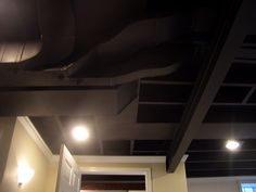 Clever way to avoid installing a ceiling in order to preserve headroom. Black paint on beams, pipes and ductwork keeps these elements exposed but de-emphasized. Fresh crown molding lightens things.