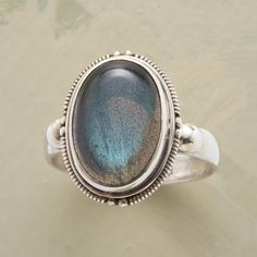 TWILIGHT RING--In this labradorite cabochon twilight ring, ambient light catches in the smooth stone, surrounded by a patterned sterling silver bezel. Whole and half sizes 5 to 9.