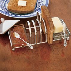 Silver toast rack with open crystal butter dish, lidded jam dish, and slots for 4 pieces of toast.