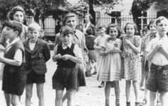 """A photograph of Jewish children in the Theresienstadt ghetto taken during an inspection by the International Red Cross. Prior to this visit, the ghetto was """"beautified"""" in order to deceive the visitors. Czechoslovakia, June 23, 1944."""
