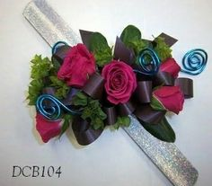 Hot pink sweetheart roes, bupleurum filler, brown ribbon and blue wire swirls on a silver snap bracelet. Prom / homecoming flowers on a wrist corsage. Dick Adgate florist original