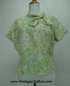 1960's floral pattern mod shift blouse by 'Judy Bond' in hues of green, white, yellow and blue with button up back and beautiful neck bow