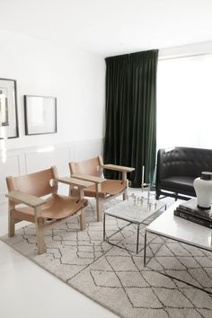 monochrome living room with Spanish chairs in tan leather and dark green velvet…