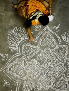 """Woman making a kolam in south India: """"Especially during the harvest season, you'll see many women making kolams outside their homes in the morning. Kolams are beautiful patterns made from rice flour. Besides for decoration purposes it was a way to feed birds and critters. A way to honor that all life is sacred and a tribute to harmonious co-existence."""""""