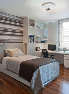 O escritório Krakowiak & Tavares Arquitetura preencheu o espaço acima da cabeceira com papel listrado. Observe que as cores repetem os tons da roupa de cama e contrastam agradavelmente com o piso de madeira.