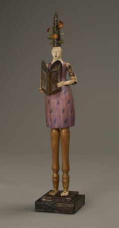 """""""Spotted Woman and Butterfly"""" wood sculpture cCreated by Elizabeth Frank - one of a kind. This piece is carved from aspen and reclaimed wood. The base is covered with layers of antique tin. The figure is painted with acrylic and finished with wax. It holds a book made of mica and antique tin with the found wings of a Monarch Butterfly pressed inside the pages. The Spotted Woman follows the path of the Monarch Butterfly. On her journey she encounters both flowers and thorns, difficulty and…"""