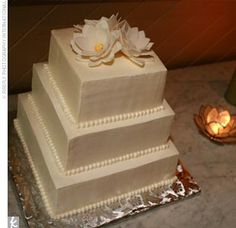 The couple cut into a three-tiered, square white cake with white buttercream frosting and two different fillings: marzipan and raspberry filling and mocha filling. Three lotus flowers sculpted from pastiage topped the confection.