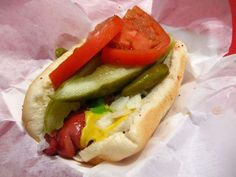 "Chicago is not just known for its famous pizza, but also for it special  hotdogs. At the Wiener Circle, the dog with ""the works"" is a grilled Vienna Beef sausage on a warm poppy seed bun, topped with mustard, onions, relish, dill pickle spears, tomato slices, and sport peppers - plus a final dash of celery salt. Do NOT ask for ketchup and expect verbal abuse from the workers as it is all part of the atmosphere. <3 nana gloria  www.wienercircle.net"