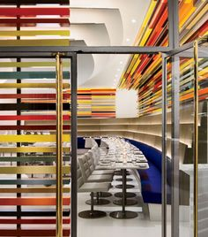 """The Wright, Andre Kikoski Architect, New York City  The rich, warm hues of artist Liam Gillick's installation — meant to be understood as a """"series of horizons"""" — form a modulating transparent skin at the entrance and around the two exterior walls of the dining room."""