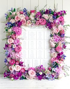 A traditional seating chart framed by pink and purple flowers