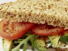 Rebana el tomate y el aguacate (puedes agregar cebolla si lo deseas) y colócalo en un plato extendido. Rocía con unas gotas de vinagre blanco, sazona con limón, sal y pimienta.   Unta el pan con mostaza y coloca el queso panela (sazona con pimienta). Agrega el aguacate y el tomate. Si lo deseas, puedes usar un poco de jamón o incluso tocino. Añade lechuga, espinaca o cualquier verdura.