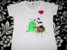 One-of-a-kind hand-painted Dino & Panda t-shirt from my series of 100 T-shirts back in 2012.   Panda gives Dino a surprise kiss on the forehead.  Size: Large V-Neck
