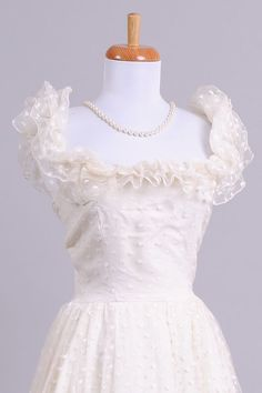 Designed in the 70's, this gorgeous vintage wedding gown is done in a white polka dotted netting over a silk satin lining of the same tone.  The sleeveless b...