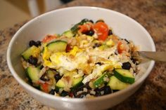 VEGGIE FRIED RICE: 1 zucchini, cut into bite sized pieces    1 handful cherry tomatoes, halved    1 can low-sodium black beans, rinsed    2 cups cooked rice    ½ cup chicken or vegetable broth    4 eggs    Your choice of cheese (shredded cheddar or Parmesan work well!)    1 teaspoon olive oil    Salt and Pepper