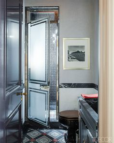 The metallic-and-marble shower door and vanity in this Steven Gambrel-designed Manhattan home are custom-designed, and the floors and shower feature tiles by Mosaic House.   - ELLEDecor.com