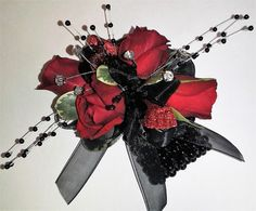 Prom corsage in red and black. Red spray roses, rhinestones, red sparkle mesh ribbon, black ribbon, and black bling. #WeDeliverTheWow