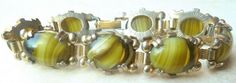 A Vintage bohemian art glass style panel bracelet The bracelet is formed from gold tone metal with eight panels Each panel has a centrally set