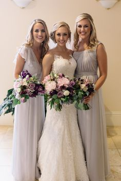 bride and her bridesmaids in pale grey gowns carry their bouquets of light pink peony, ocean song rose, dark purple stock, dried lavender, light pink ranunculus, lavender lisianthus, dusty miller, burgundy scabiosa, pink wax flower, white majolik spray rose, bay leaf, and silver dollar eucalyptus wrapped in cream satin ribbon