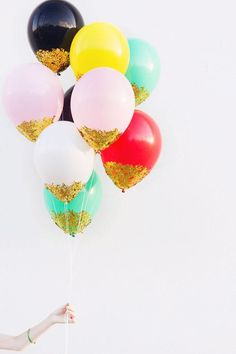 Just put glue around the bottom of your balloons and sprinkle gold glitter on them! gold balloons!