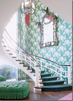 I love this space!  The curve of the stair, the bright patterned walls and the elaborate mirror make this so much fun!