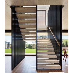 """Oftentimes, #staircases are situated to the side of a #home but Bates Masi + Architects utilized this opportunity to create """"walls"""" that divide the main dining room (right) from the kitchen (left). Photo by Michael Moran"""