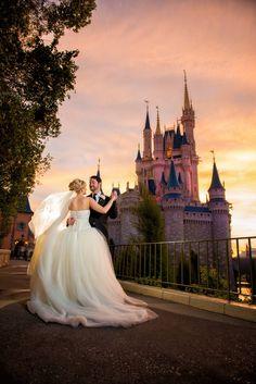 Sabia que é possível fazer seu casamento na Disney? Clique para ver os pacotes e valores! Na foto, noivos em frente a um castelo.