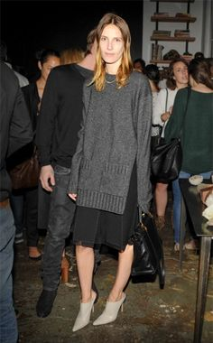 Long grey sweater layered over a knee-length black skirt
